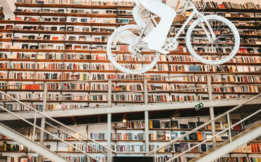 Inside of a library with a bicycle sculpture hanging from the cieling