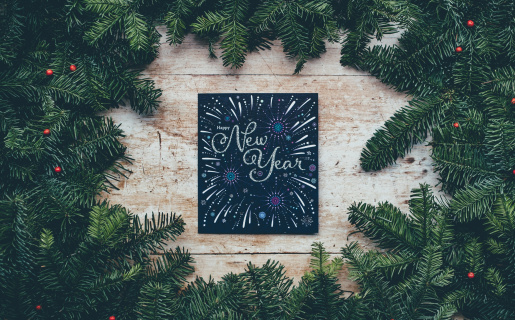 """holiday pines with a chalkboard sign in the center that says """"New Year"""""""