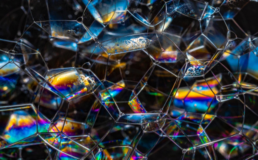 rainbow-colored glass that looks like honeycomb with light hitting different parts