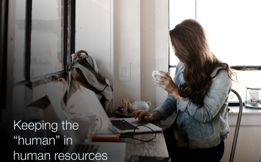 """A woman sitting at her desk drinking coffee with text overlaid that says, """"Keeping the 'human' in human resources"""""""