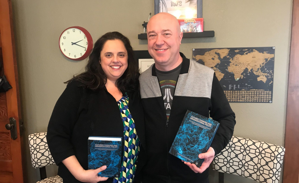 Yvette and Frank hold a textbook that they are published in