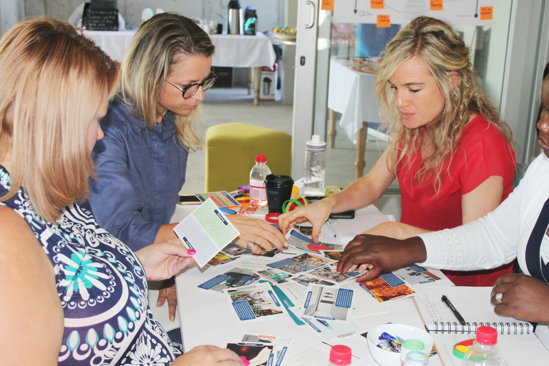 A group of several participants work together at a table using Wicked Opportunities Trend Cards. This is a candid photo from our Applied Foresight Accelerator Session