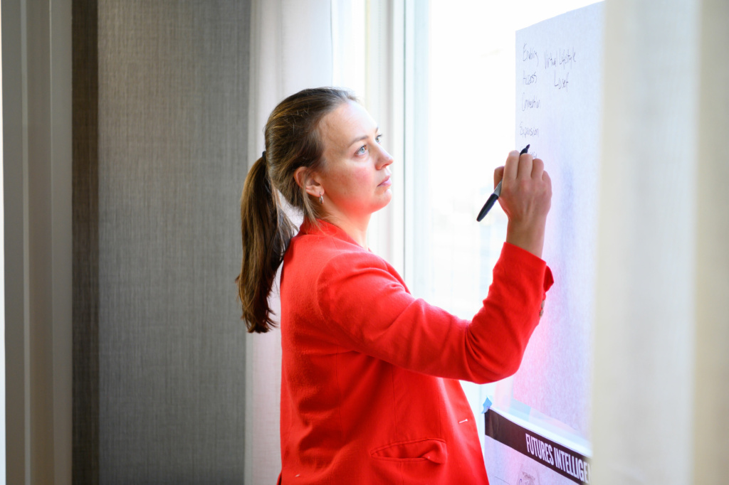 Certified Foresight Practitioner Katie McPherson writes on a chart in a bright red blazer. She has set herself apart with a CFP designation.